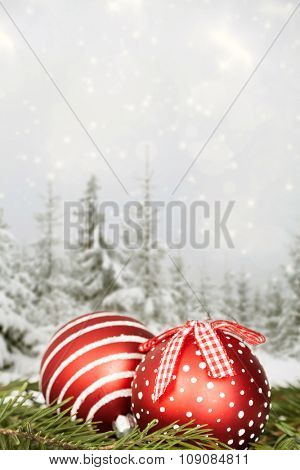 Red Christmas balls in the snow, snow cowered pine trees in the background