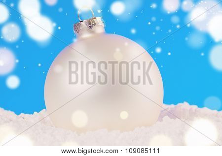 white decorative christmas ball on snow against blue festive background