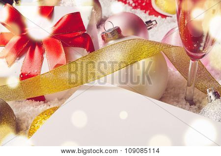 greetings card among white decorative christmas gift box with ribbon and balls on snow, view from above