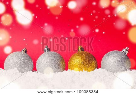 silver and golden decorative christmas balls on snow against red festive background