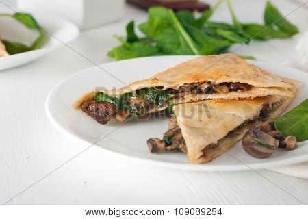 mushroom spinach quesadilla cut into pieces and arranged on white plate, overhead shot