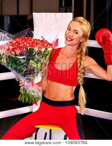 Happy girl boxer wearing red gloves with bouquet flowers sitting in corner of boxing ring.
