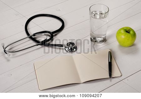 Open Notebook With Pen, Stethoscope, Apple And A Glass Water