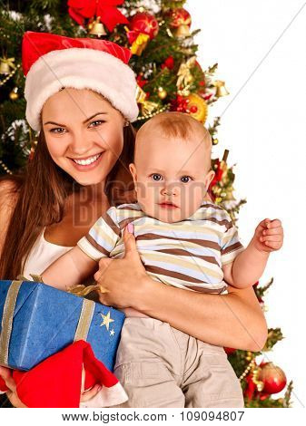 Mom wearing Santa hat holding  baby with blue gift box  under Christmas tree. Isolated.