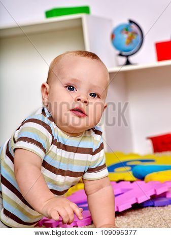 Kid baby boy lying on floor and plying with puzzle toy. Early education.