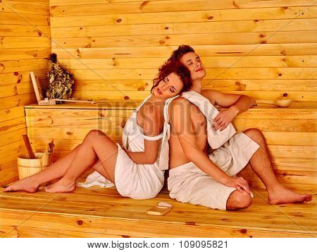 Couple of man and woman  in hat  relaxing at sauna.