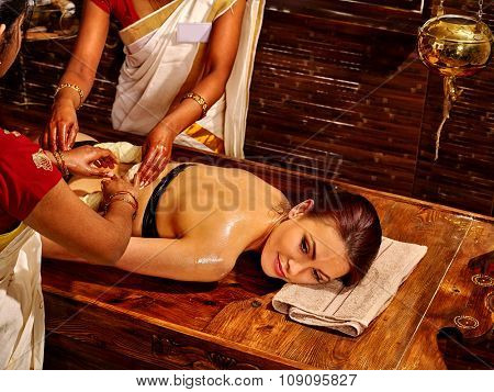 Young woman having back dough Ayurveda spa treatment massage.