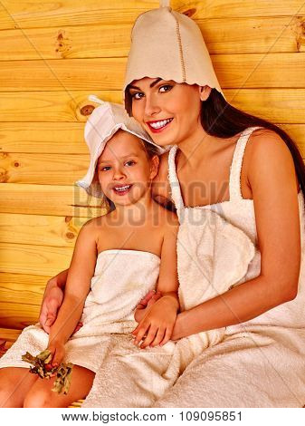 Happy family with child and mother relaxing at sauna.