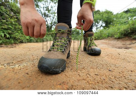 young woman hiker tying shoelace