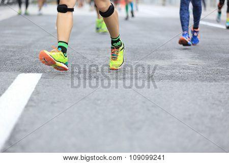 marathon runner legs running on city road