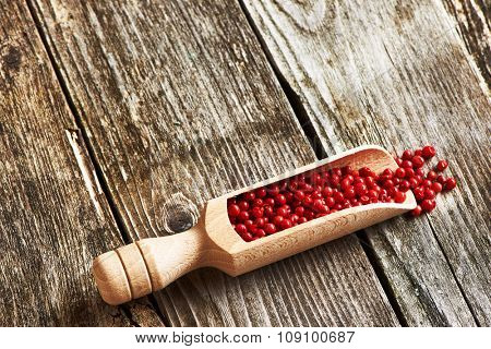 Wooden scoop with rose pepper over rustic background
