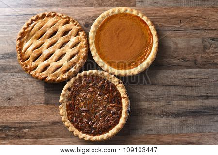 Three pies for Thanksgiving on a wood surface. The desserts include apple, pumpkin and pecan pies - all traditional treats for the American Holiday.