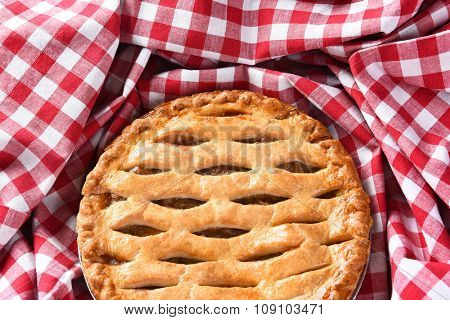Closeup of a fresh baked Apple Pie surrounded by a red and white checked table cloth.