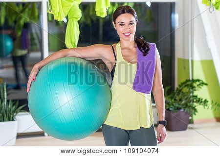 Woman holding fit ball resting after workout pilates training.