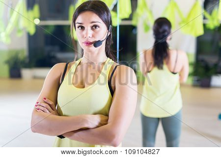 Female sports trainer with microphone Fit woman standing at fitness club.