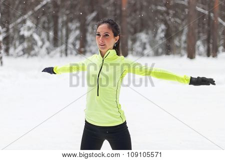 Young sportswoman stretching and preparing to run. woman doing sports outdoors winter park.