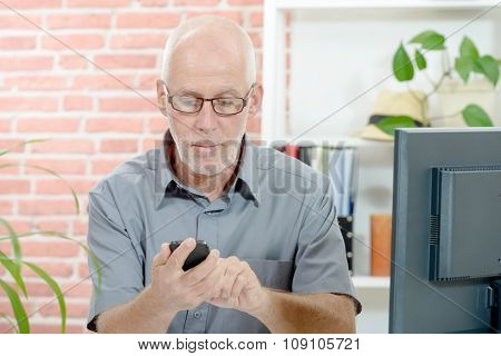 Middle Aged Businessman Sitting At Desk, With  Phone