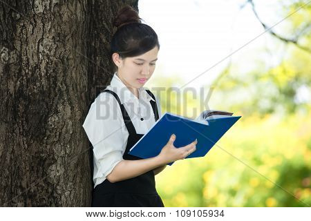 Asian Student Reading Blue Book, Against Green Of Summer Park.