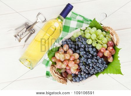 White wine bottle and grapes on white wooden table. Top view