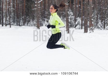 Athlete running fit woman Sporty girl jogger warming up jumping Winter park forest.