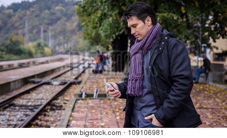 Businessman With Smartphone At Train Station