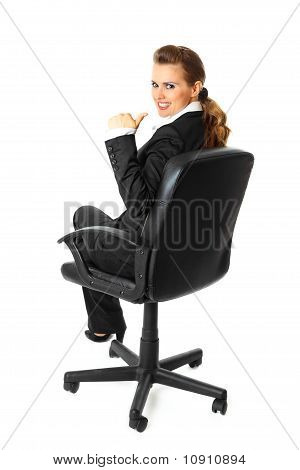 Smiling modern business woman sitting on chair and showing thumbs up gesture
