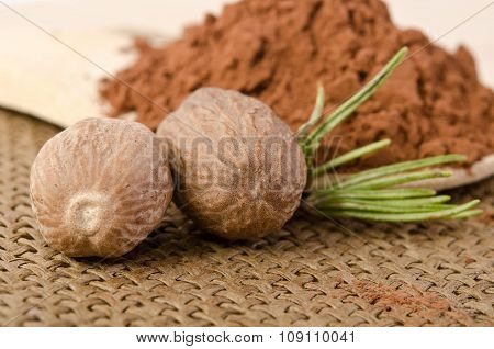 Nutmeg With A Sprig Of Rosemary And Cacao Powder In The Wooden Spoon On Sacking Background