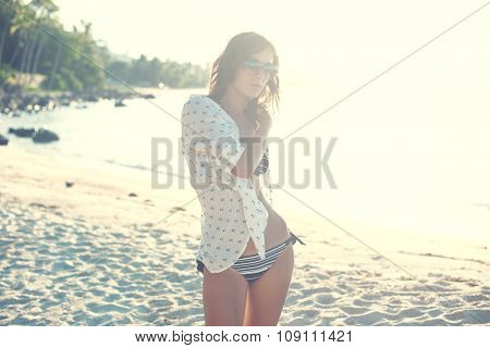 Young woman enjoying sunny day on tropical beach toned instagram filter.