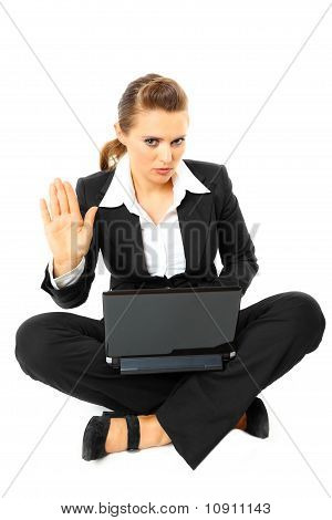 Sitting on floor with laptop serious modern business woman showing stop gesture