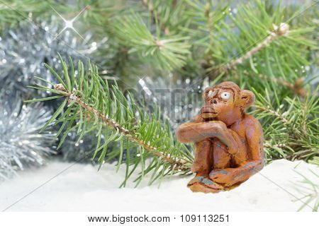 dreamy merry monkey from clay pottery sits near the tree in the snow