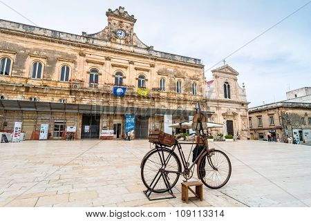 Old Knife Grinder Bicycle And Main Square In Ostuni, Italy