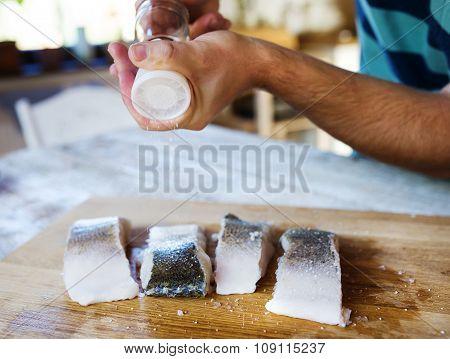 Man seasoning zander fillets
