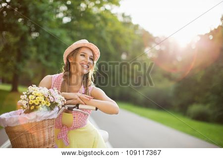 Smiling girl on a bicycle in the park