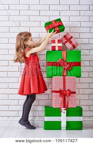 Happy little girl with Christmas gifts at a blank brick wall.