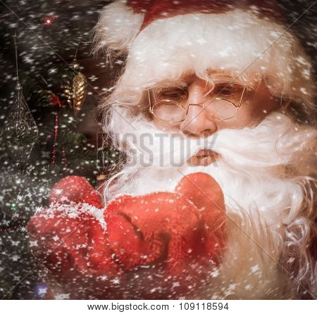 Santa Claus in wooden home interior blowing snow from his hands