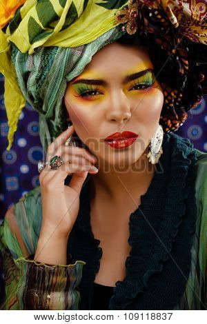 beauty bright woman with creative make up, many shawls on head like cubian woman, ethno look