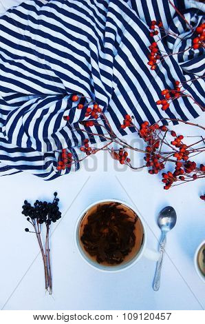 Branches with red berries hawthorn. and white cup of tea on white bakground, cup of tea with hip ros