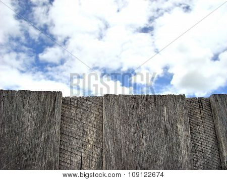Clouds beyond old wood fence