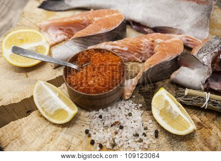 Fresh Norwegian rainbow trout with lemon red caviar, sea salt and onions on a wooden background.