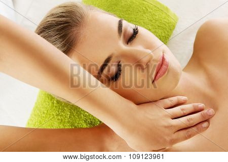 Young smile relaxed woman is massaged on massaged table.