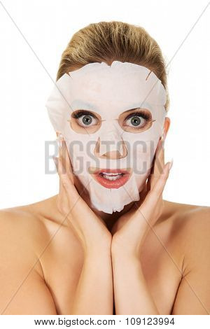Young surprised woman with facial mask,isolated on white.