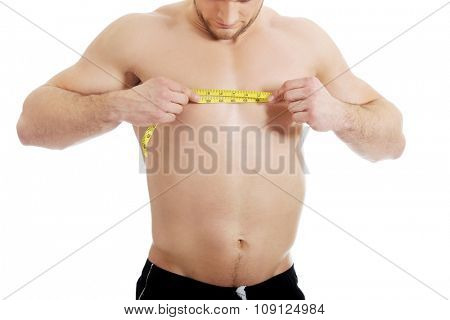 Handsome muscular man measuring his chest.
