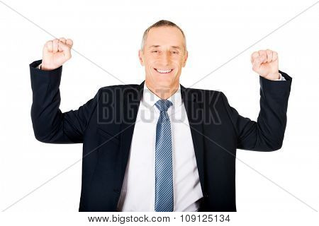 Successful mature businessman celebrating with arms up.