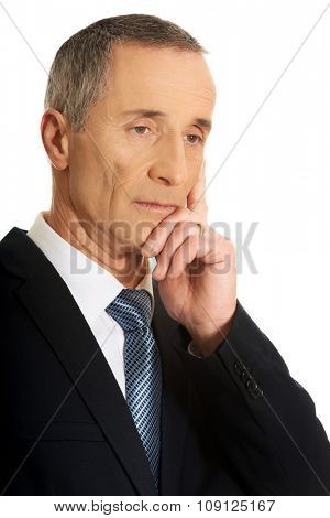 Portrait of a pensive businessman touching chin.
