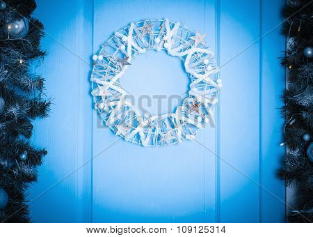 Christmas Wreath On A Rustic Wooden Front Door. Blue Toned