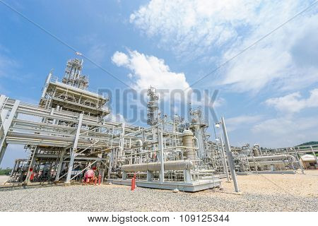 oil refinery stands in empty ground in cloudy sky