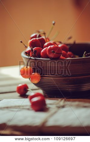 fresh ripe cherries on plate with wrapped gift on wooden table, country living concept