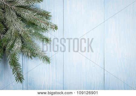 Christmas Fir Branch In Snow On Wooden Background