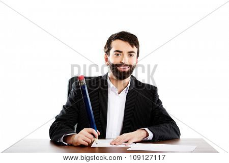 Happy businessman writing with big pencil in the office.