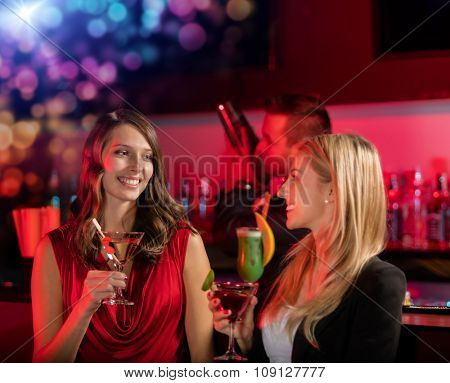 Two girls at the bar with cocktail drink, having fun